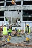 Um grupo de trabalhadores da construção que derramam o concreto molhado Imagens de Stock Royalty Free