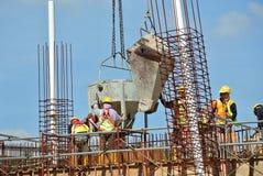 Um grupo de trabalhadores da construção que derramam o concreto molhado Fotos de Stock