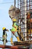 Um grupo de trabalhadores da construção que derramam o concreto molhado Imagens de Stock