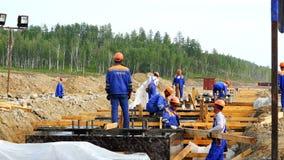 Um grupo de trabalhadores e os construtores executam o trabalho da instalação nas fundações da construção vídeos de arquivo