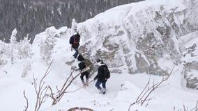 Um grupo de turistas desce da parte superior de uma montanha coberto de neve vídeos de arquivo