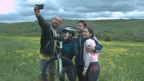 Um grupo de turistas felizes faz um selfie em um prado da flor em um campo bonito com nuvens grossas Bonito novo filme
