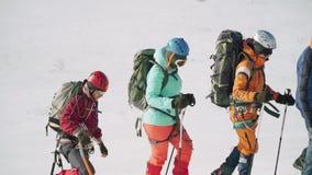Um grupo de turistas segue-se ao longo do trajeto em sapatos de neve e no equipamento os tropeços os mais atrasados e ele do turi video estoque