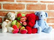 Um grupo de ursos de peluche bonitos que sentam-se junto contra com o papel de parede Foto de Stock