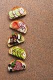 Um grupo de vários sanduíches com salmões, a salsicha fumado, os vegetais e o queijo de feta em um fundo de pedra marrom Vista su fotos de stock royalty free