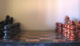 Um grupo de xadrez de pedra com partes vermelhas e pretas, apronta-se para começar imagens de stock