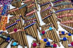 Um grupo de zamponas (flautas da bandeja) para a venda no mercado indiano em Otavolo em Equador imagens de stock