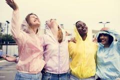 Um grupo diverso de adolescentes nas capas de chuva fora imagens de stock