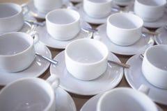 Um grupo do grupo dos copos de café cerâmicos brancos a preparar-se para um café Foto de Stock