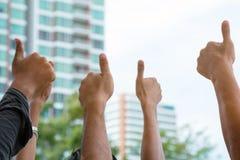 Um grupo do polegar aumentado dos povos fotografia de stock