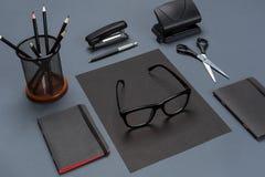 Um grupo dos acessórios pretos do escritório, vidros no fundo cinzento Imagens de Stock Royalty Free