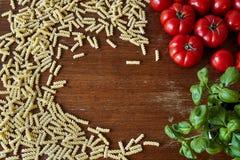 Um grupo dos tomates e das ervas da massa que dão o espaço foto de stock royalty free