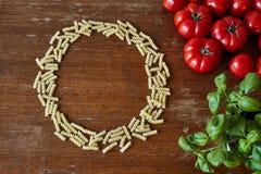 Um grupo dos tomates e das ervas da massa que dão o espaço Fotos de Stock