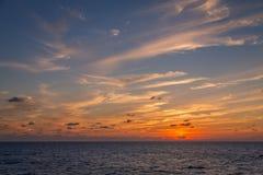 Um grupo dramático de nuvens que derivam sobre as águas tropicais do mar das caraíbas é iluminado nos últimos momentos da luz do  imagem de stock