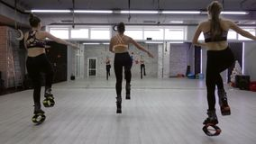Um grupo fêmea de três novos, meninas 'sexy' Kangoo salta no gym vídeos de arquivo