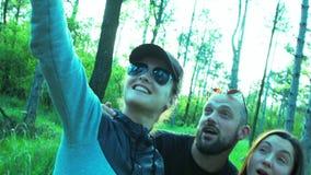 Um grupo feliz de amigos faz o selfie na natureza Homem novo bonito e jovens mulheres que têm o divertimento, selfie em um smartp video estoque