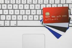Um grupo fora dos cartões de crédito e dos cartões de banco em uma chave do portátil do computador Imagem de Stock