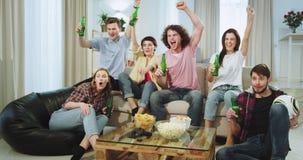 Um grupo grande de amigos carismáticos na frente da tevê que olham um fósforo de futebol e que bebem a cerveja são excitados assi filme