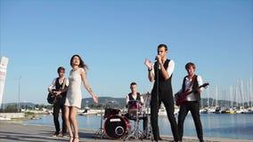 Um grupo juvenil adulto de músicos dá um concerto perto do mar no dia vídeos de arquivo