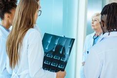 Um grupo multirracial de internos médicos com fotografia do raio X que escutam fotos de stock royalty free