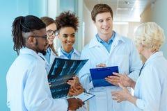 Um grupo multirracial de internos médicos novos que escutam um doutor mais idoso na Imagem de Stock Royalty Free