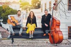 Um grupo musical de três povos que sentam-se em um banco na rua A faixa consiste em dois homens e em uma menina Homens com baixo  imagens de stock royalty free