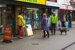 Um grupo pequeno de proprietários do cão reune-se e conversa-se fora da loja de animais de estimação local em Hythe em Hampshire  foto de stock