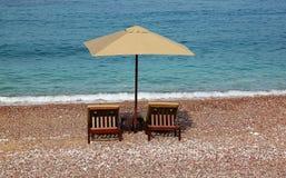 Um guarda-chuva e dois de praia encalham camas na costa de mar Imagens de Stock Royalty Free