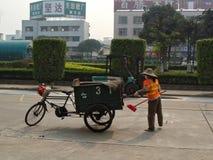 Um guarda de serviço fêmea limpa o lixo na rua Fotos de Stock Royalty Free