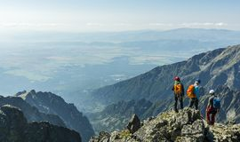 Um guia da montanha com um par de clientes em um pico de montanha fotografia de stock