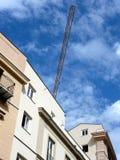 Um guindaste atrás de um telhado Imagens de Stock Royalty Free