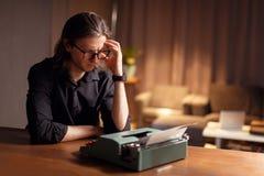 Um guionista que trabalha em um scenary O homem na camisa preta que guarda as mãos perto da cabeça, desenvolve encenações cinemát imagem de stock