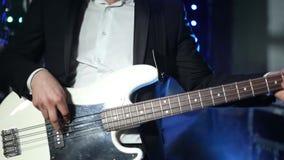 Um guitarrista joga uma guitarra elétrica em um clube video estoque