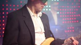 Um guitarrista joga uma guitarra elétrica em um clube filme