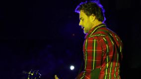 Um guitarrista novo que joga a guitarra concert Iluminação colorida video estoque