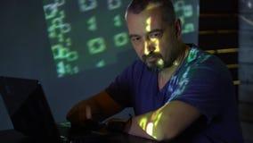 Um hacker do homem nos óculos de sol em uma sala escura trabalha com o código do programa conceito no cibercrime video estoque