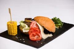 Um hamburguer da reunião serviu com queijo e vegetais Fotografia de Stock