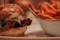 Um hamburguer do deliciouse com as fritadas doces do potaot closezup, papel de parede, roasted, carne, salat; imagem de stock