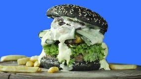 Um hamburguer suculento grande com um bolo verde polvilhado com o sésamo com verdes e um rissol da carne cercado por batatas frit video estoque