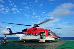 Um helicóptero a pouca distância do mar em uma plataforma petrolífera Imagem de Stock