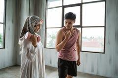 Um hijab da mulher que faz exercícios do peso com auxílio de seu instrutor pessoal imagem de stock