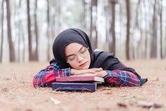 um hijab muçulmano novo sonolento do preto da mulher e uma camisa escocesa que leem um livro fotos de stock
