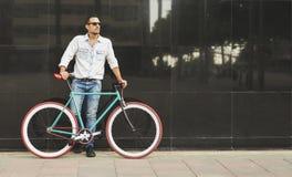 Um homem à moda novo com os óculos de sol que levantam ao lado de sua bicicleta fotografia de stock