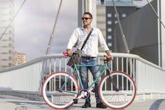 Um homem à moda novo com os óculos de sol que levantam ao lado de sua bicicleta imagens de stock royalty free