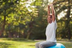 Um homem é contratado em um parque da ioga com uma bola azul da ioga Está sentando-se na bola que levanta suas mãos acima Fotos de Stock Royalty Free
