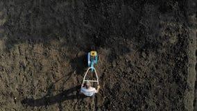 Um homem é um fazendeiro em uma área suburbana, um jardim vegetal, arados a terra com um cultivador, um arado manual do motor, ar vídeos de arquivo