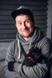 Um homem é um fotógrafo com câmera Face engraçada Escuro - fundo cinzento Lugar para o texto O fotógrafo dispara no imagem de stock