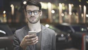 Um homem é guardando e de vista seu telefone celular Imagens de Stock