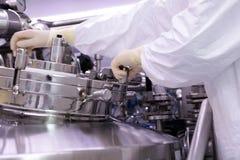 Um homem abre um reator químico Reitor da indústria farmacêutica O homem fecha o reator A produção de granula, suspen Imagem de Stock Royalty Free