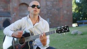 Um homem adulto calvo nos óculos de sol joga a guitarra e canta-a fora Tiro m?dio vídeos de arquivo